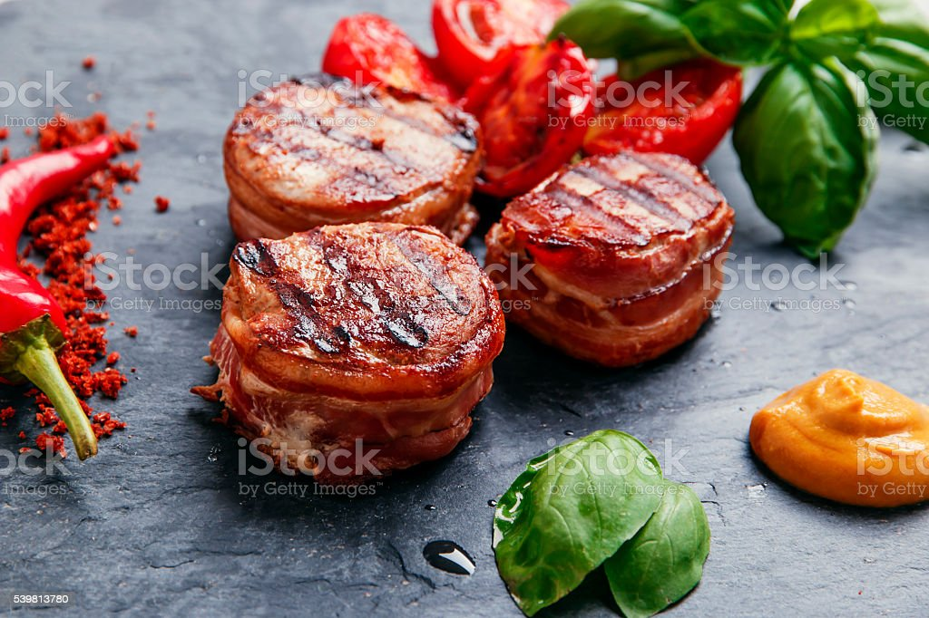Grilled meat fillet steak wrapped in bacon medallions stock photo