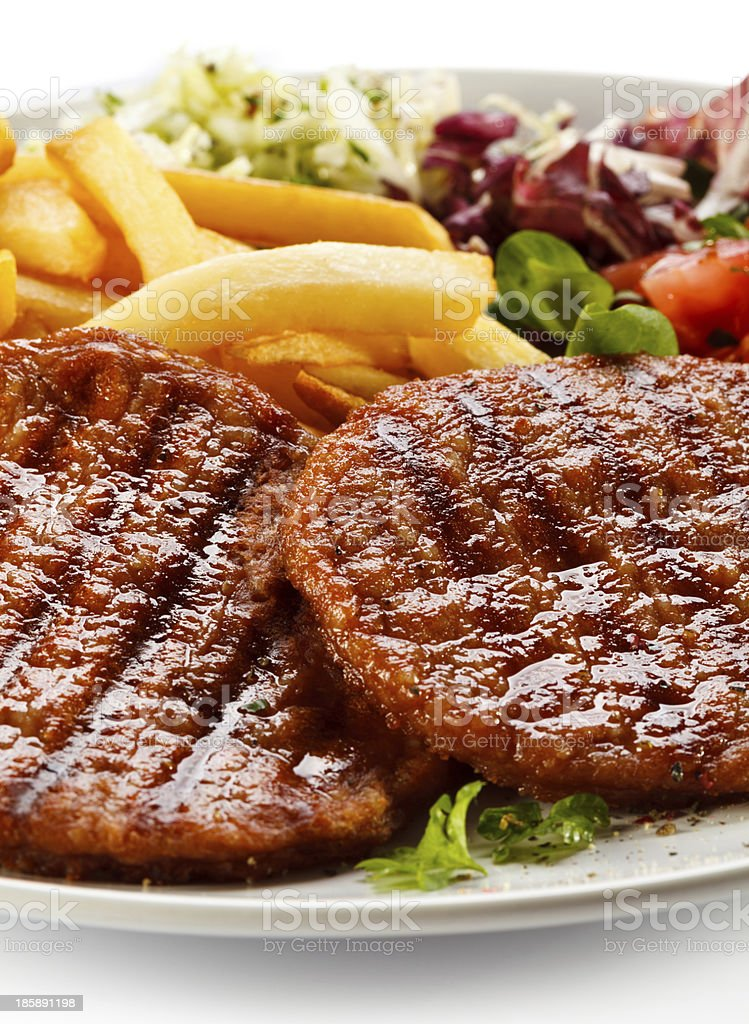 Grilled meat, French fries and vegetables royalty-free stock photo