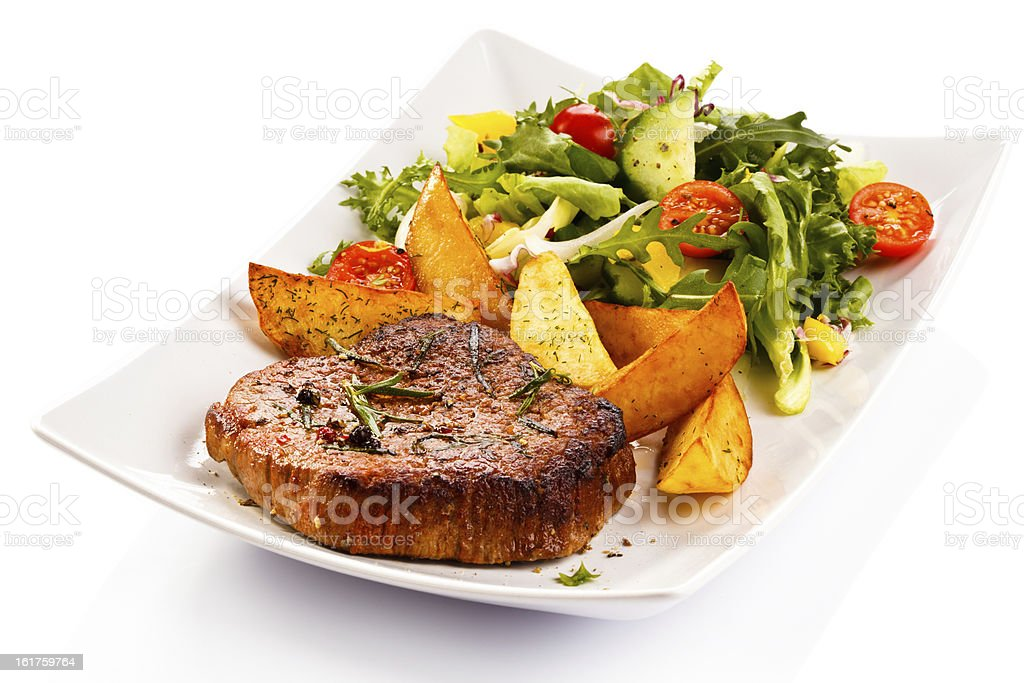 Grilled meat, potatoes and vegetables stock photo