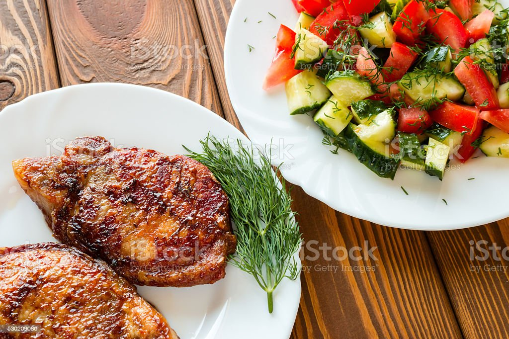 grilled meat with dill and salad with cucumber and tomato stock photo