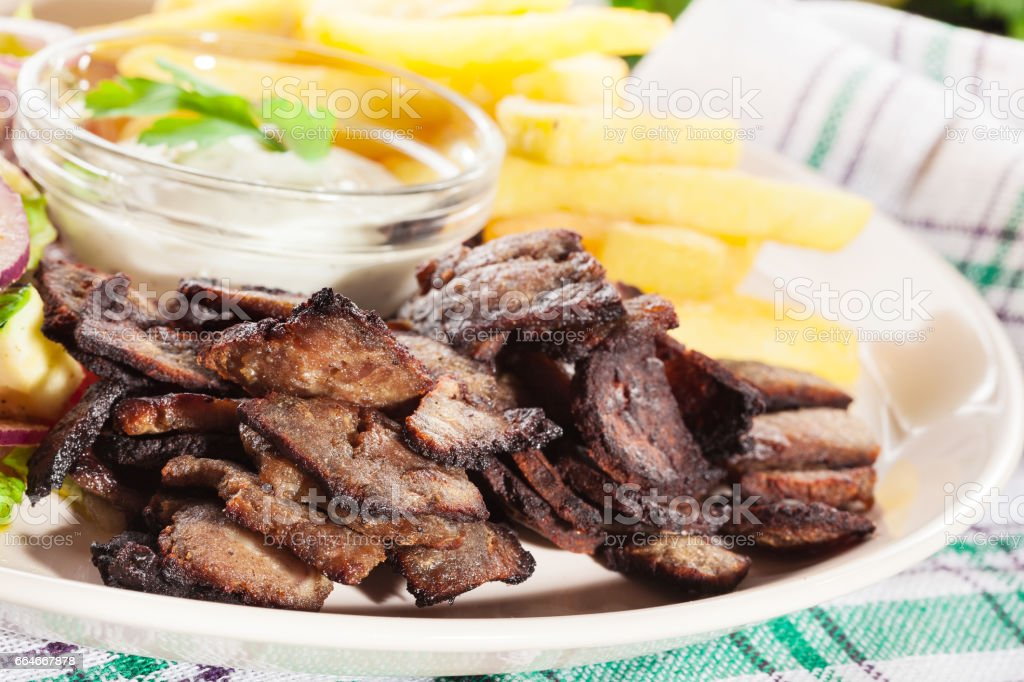 Grilled meat with French fries and fresh vegetables stock photo