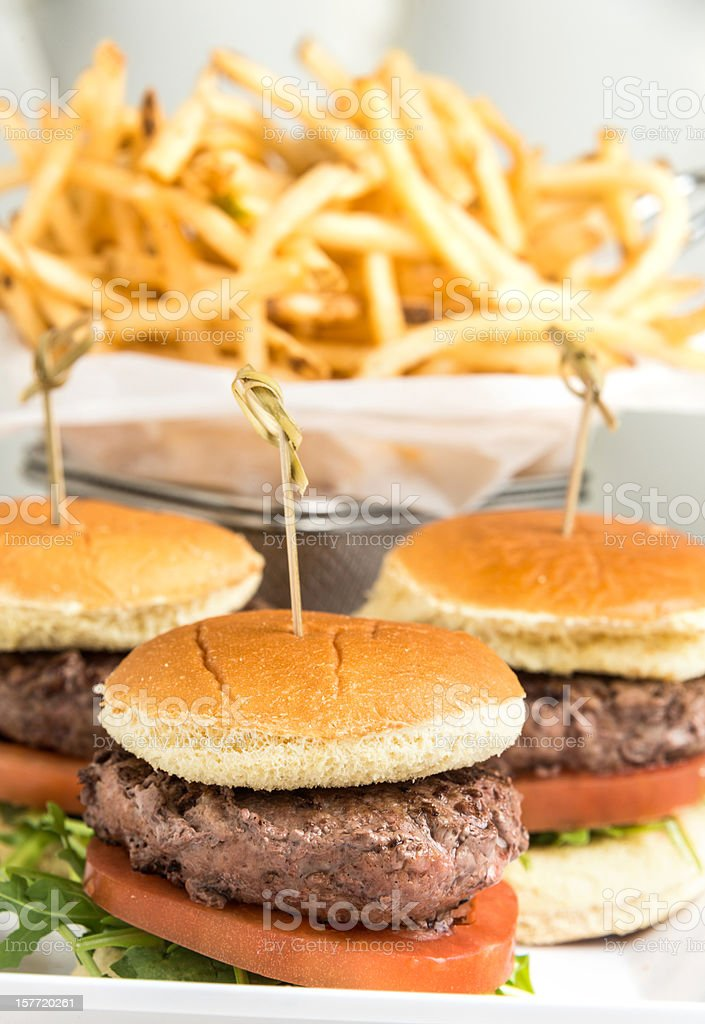 Grilled mini burgers in front of a basket of french  fries. stock photo