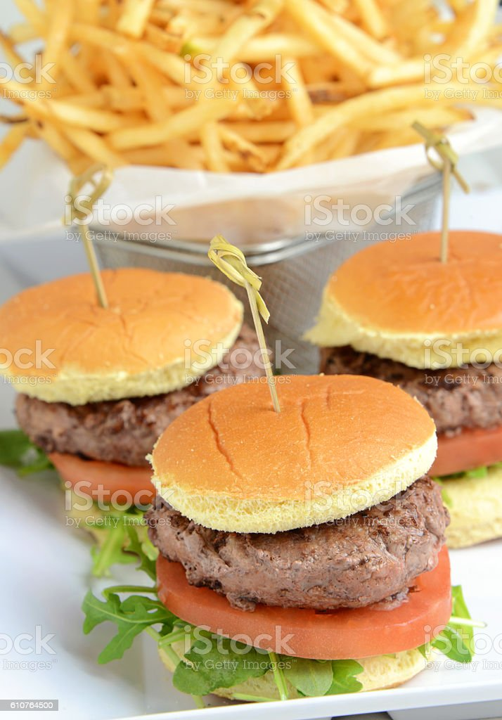 Grilled miniburgers in front of a basket of french  fries. stock photo