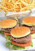 Grilled miniburgers in front of a basket of french  fries.