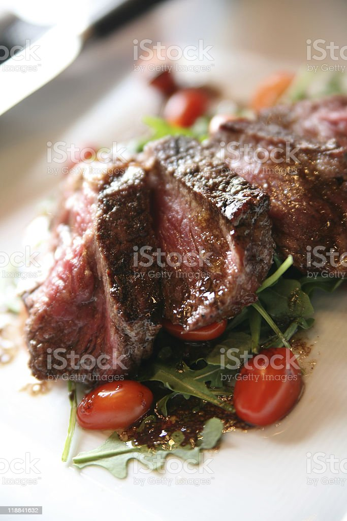 Grilled New York Strip on a bed of Arugula stock photo