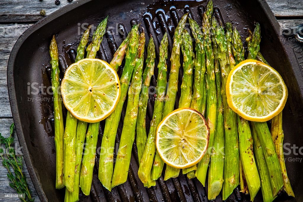 grilled organic asparagus with lemon stock photo