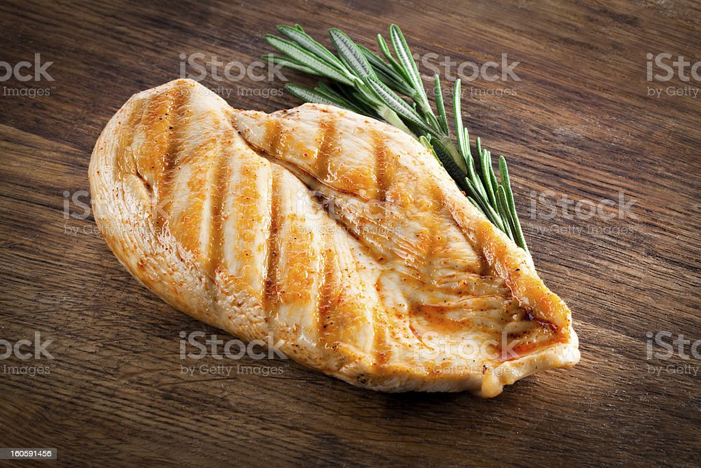 Grilled organic chicken with rosemary on wood royalty-free stock photo