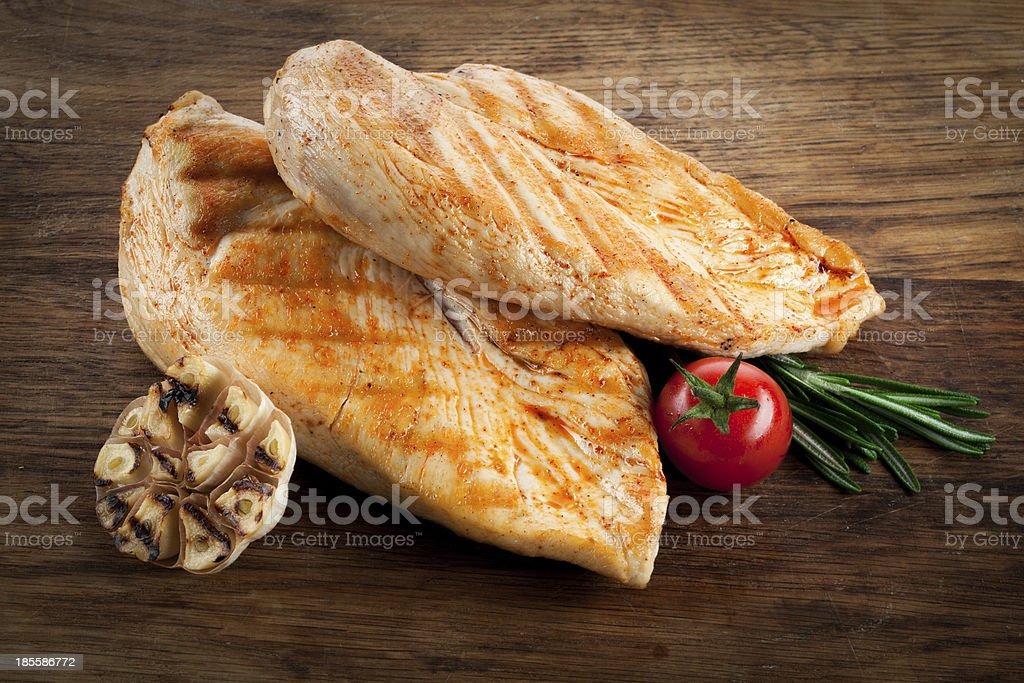 Grilled organic chicken with tomato and garlic on wood stock photo