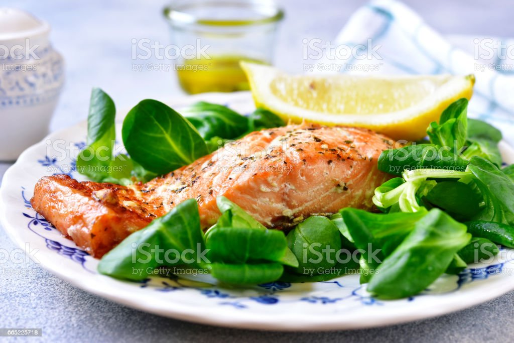 Grilled organic salmon with salad leaves on a vintage plate stock photo