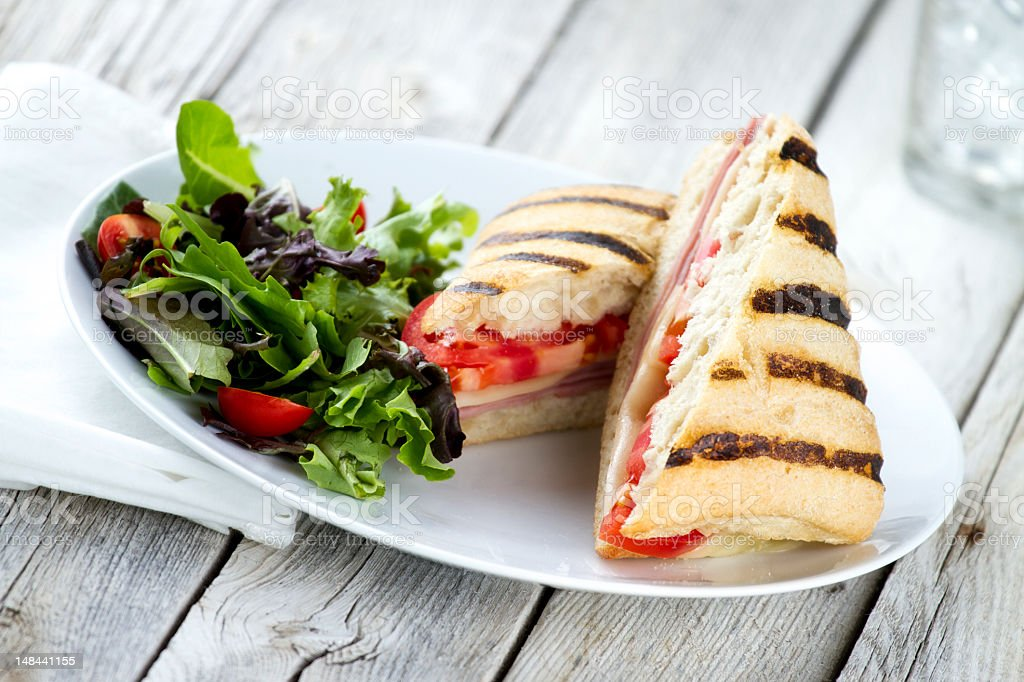 Grilled panini sandwich and salad in plate on a wood table stock photo