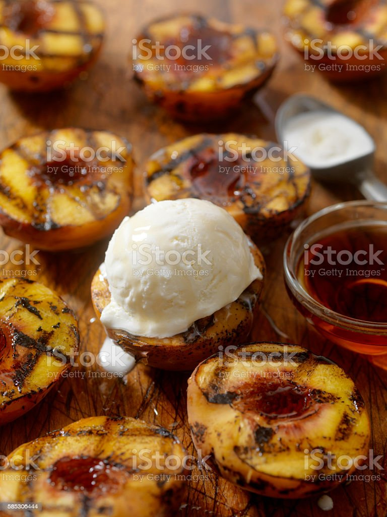 Grilled Peaches with Vanilla Ice Cream and Maple Syrup stock photo