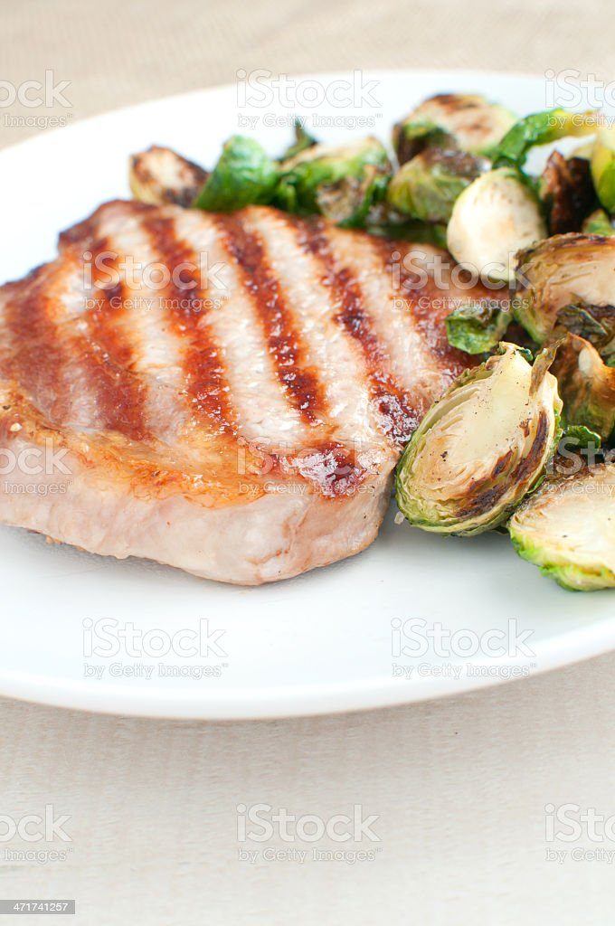 Grilled pork and brussels sprouts royalty-free stock photo