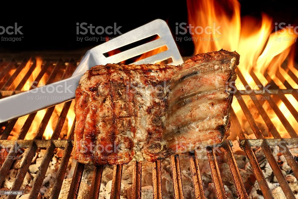 Grilled Pork Chop on Flaming BBQ Grill. stock photo