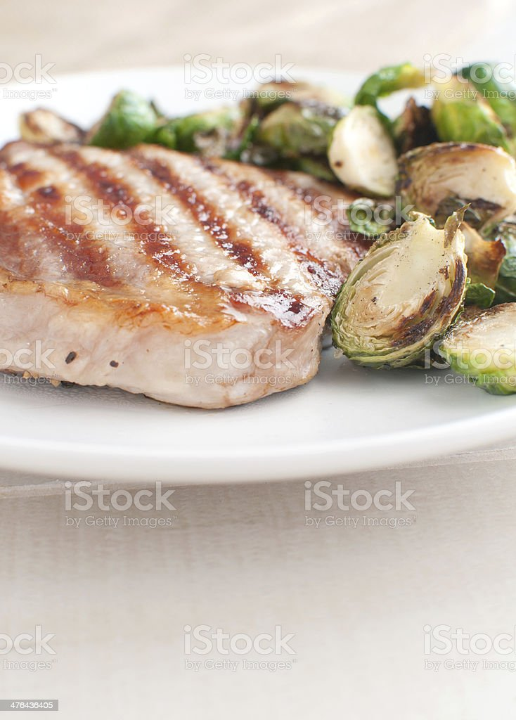Grilled pork chop with brussels sprouts stock photo