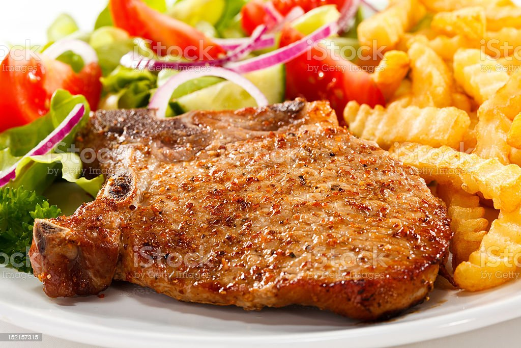 Grilled pork chop with chips and vegetables royalty-free stock photo