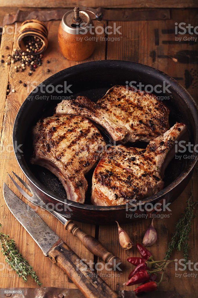 Grilled pork chop with spices in a frying pan stock photo