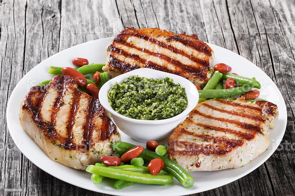 grilled pork chops on a white dish stock photo