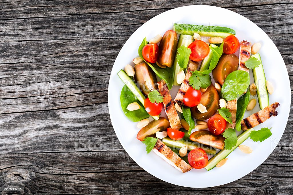 Grilled pork chops salad with vegetables and spinach stock photo