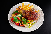 Grilled pork cutlet meat garnished with potato and salad on