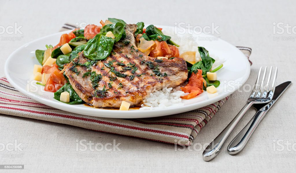 grilled pork cutlet with rice, tomato salad and basil stock photo