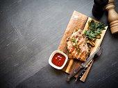 Grilled pork loin, vegetables on wooden board, black stone background