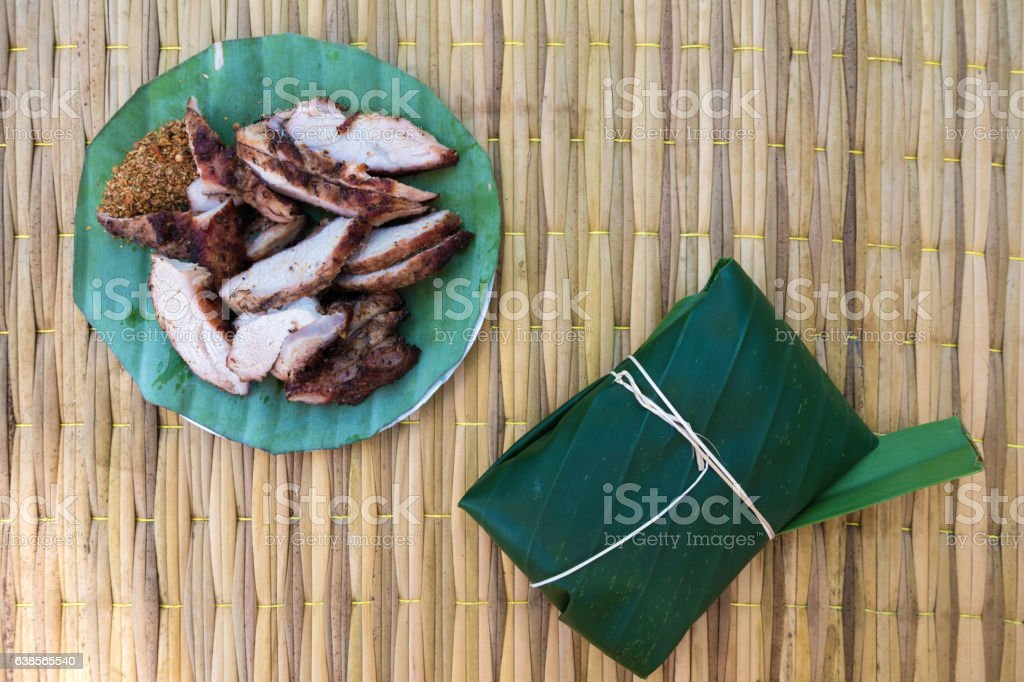 grilled pork on banana leaf package on the mat stock photo