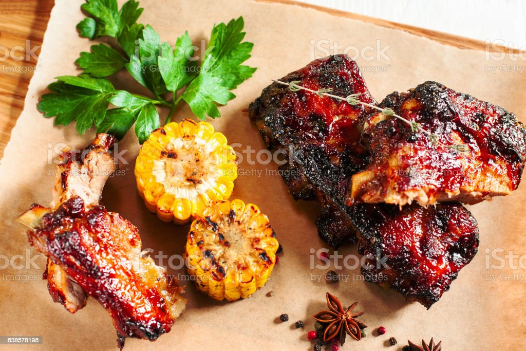 Grilled pork ribs with corn on wood flat lay stock photo