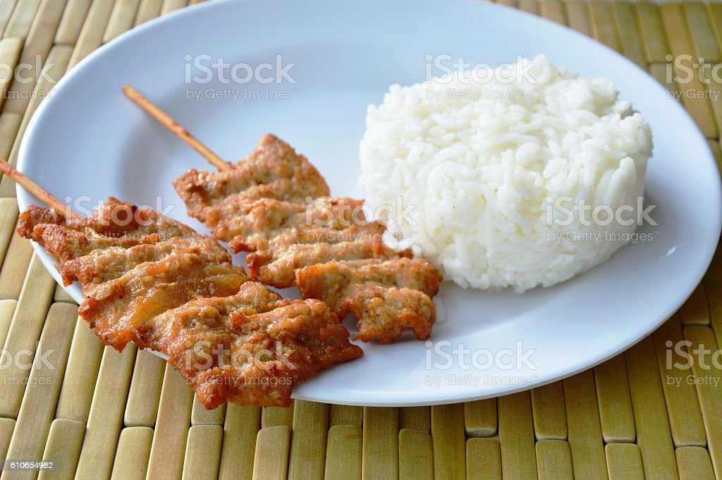 grilled pork stab in wooden stick with plain rice stock photo