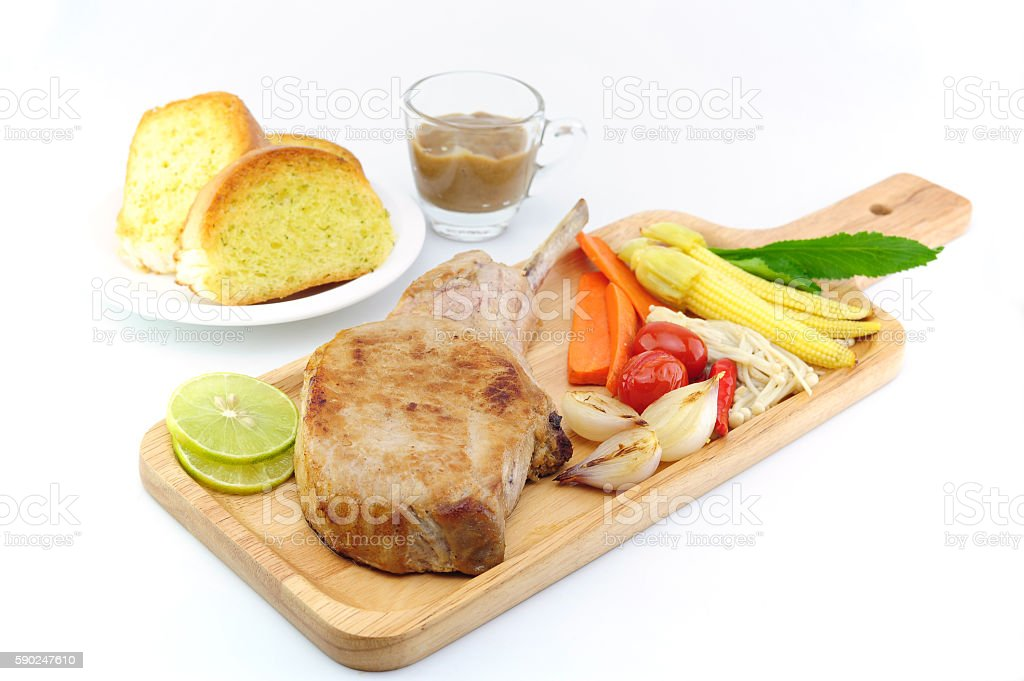 grilled pork steak with vegetable on plate wooden stock photo