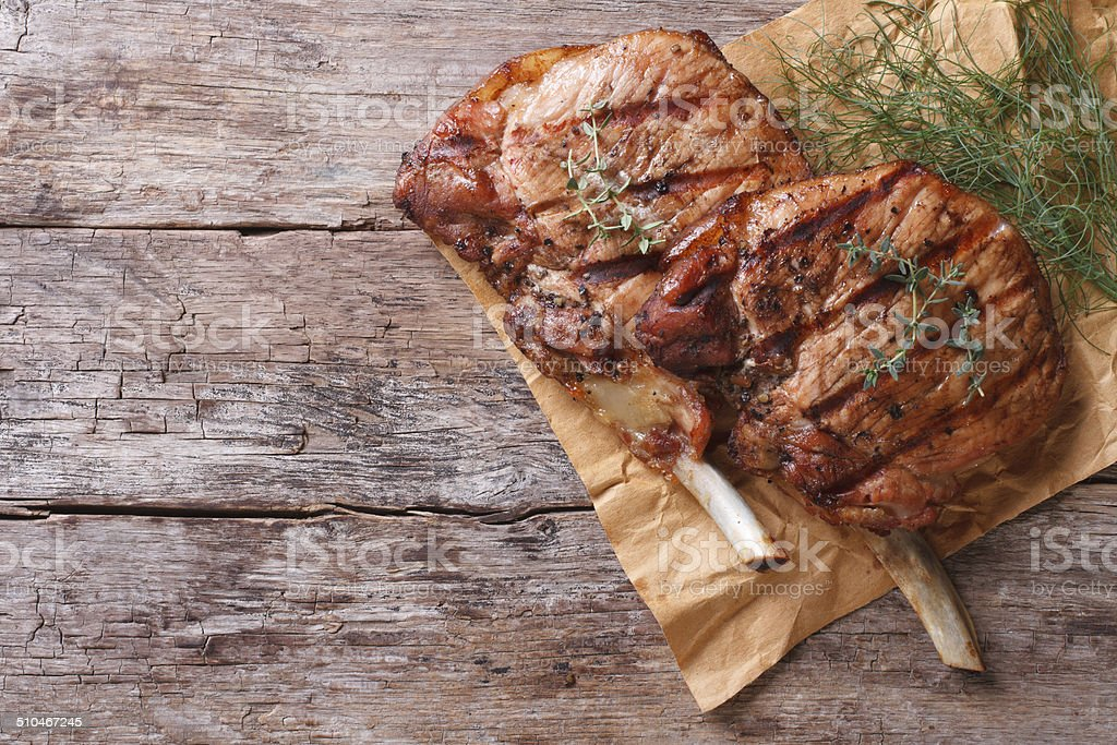 grilled pork with herbs on an old table top view stock photo