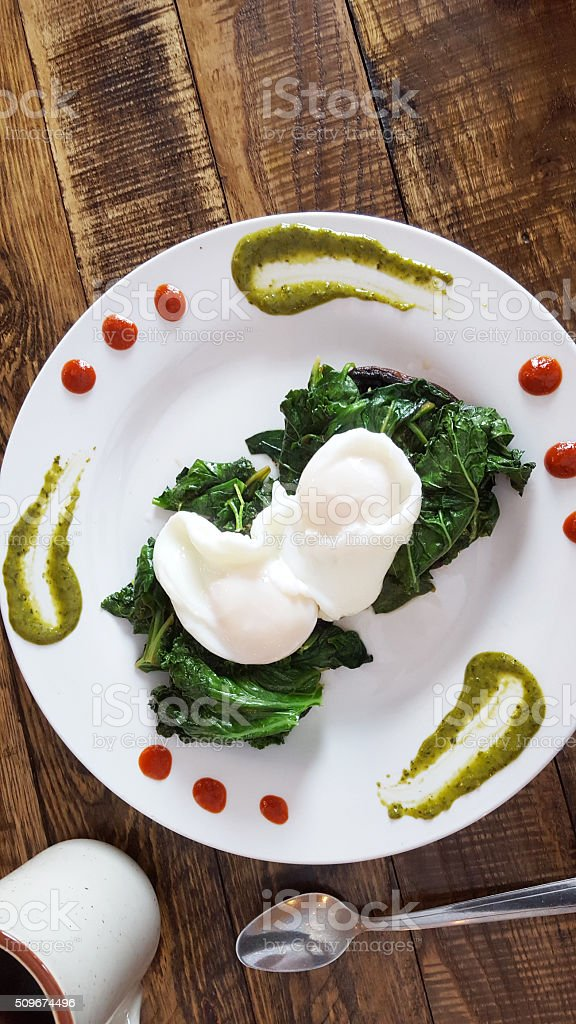 Grilled Portabello Mushrooms with Greens and Poached Eggs stock photo