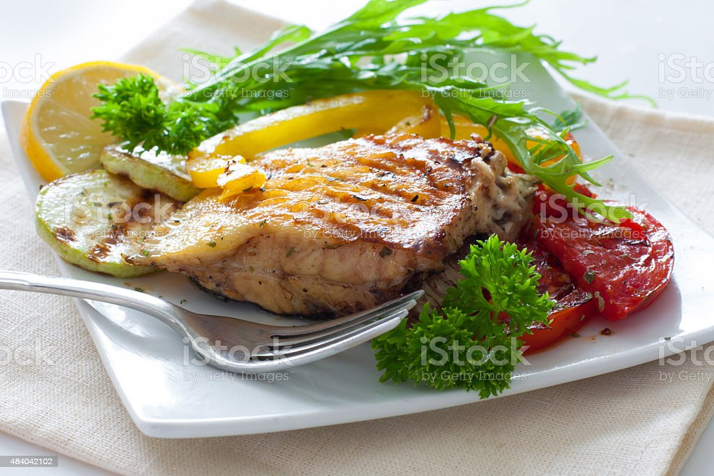 Grilled portion of flounder with vegetables stock photo