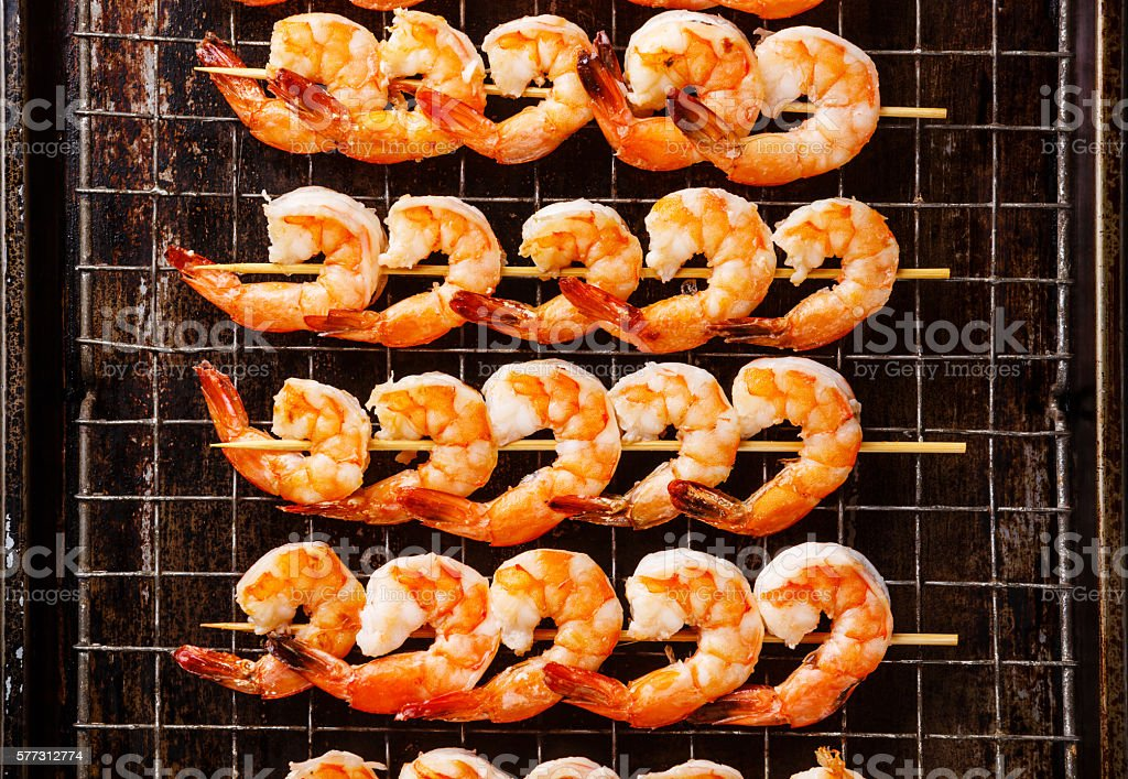 Grilled Prawns on skewers on metal grid stock photo
