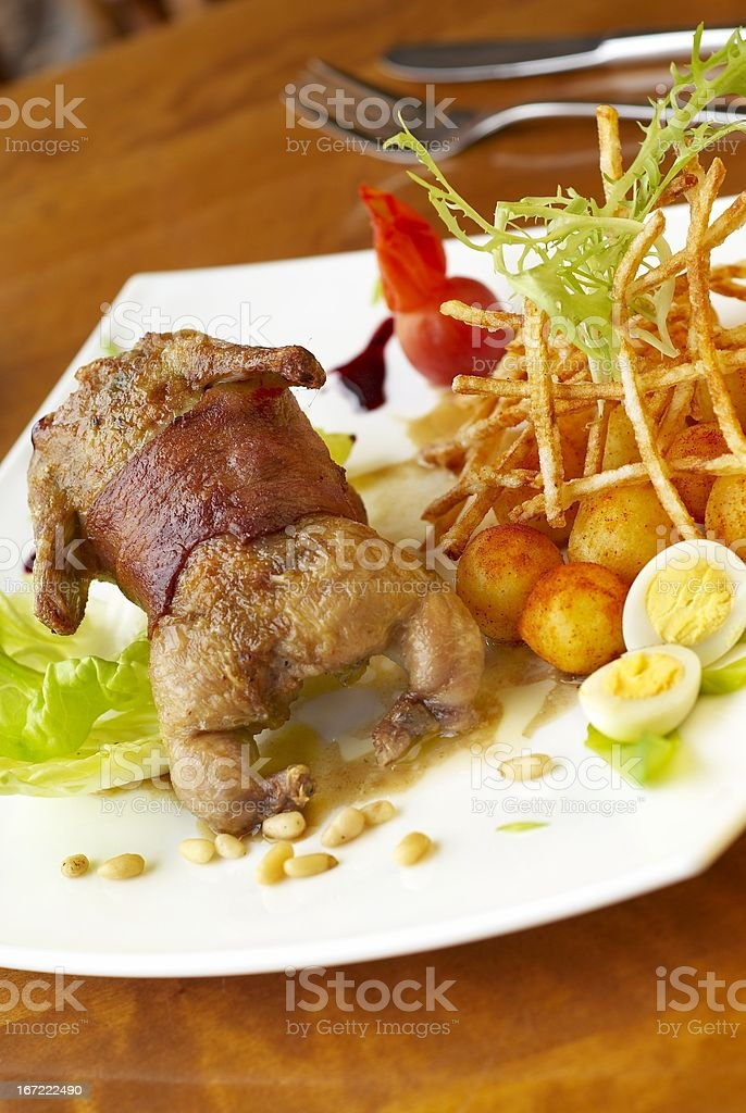 Grilled quail in bacon with fried potatoes royalty-free stock photo