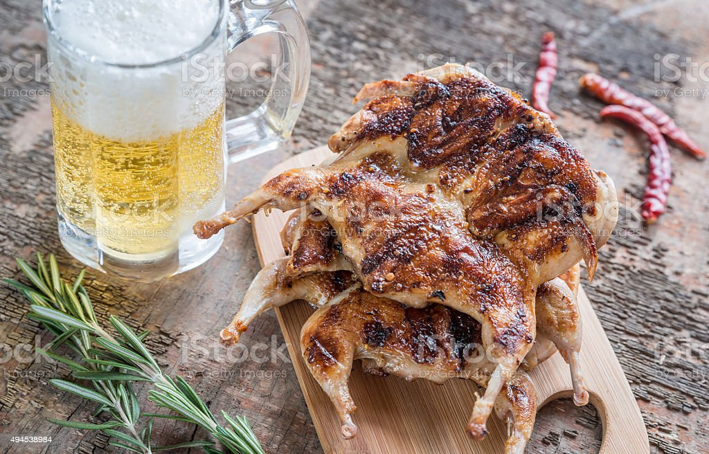 Grilled quails with glass of beer stock photo