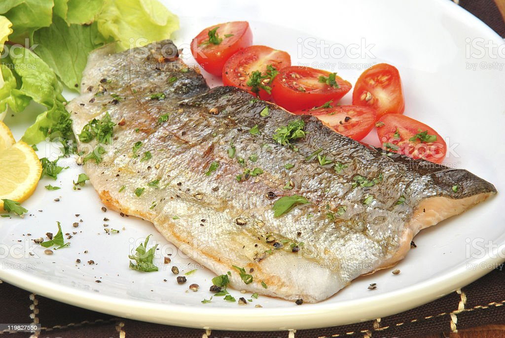grilled rainbow trout with organic tomato and parsley stock photo