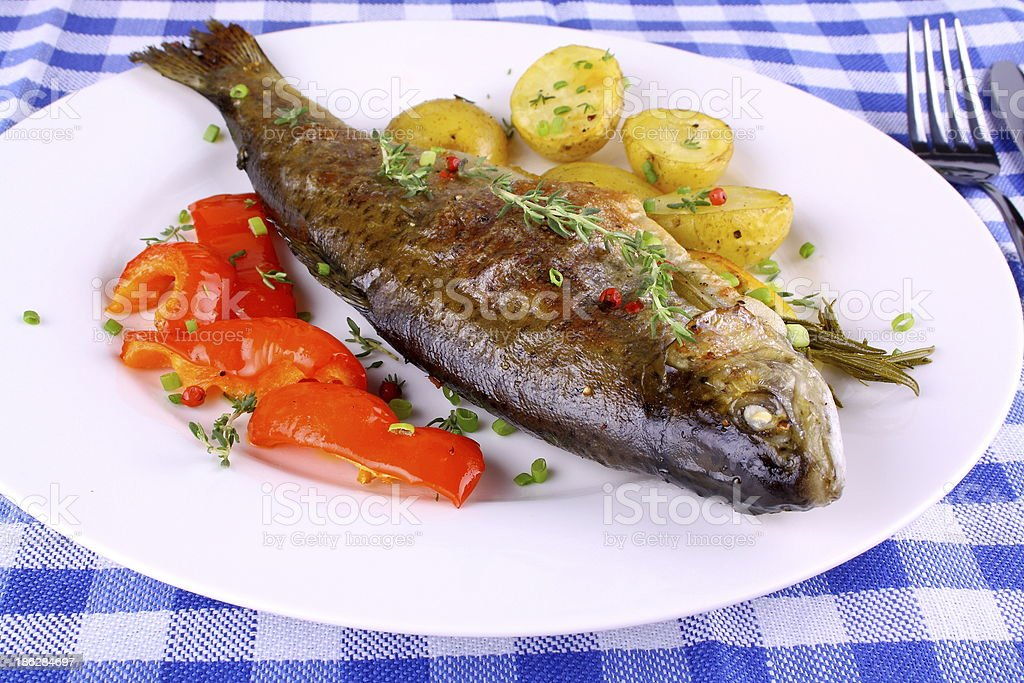 Grilled rainbow trout with red pepper, potato and herbs royalty-free stock photo