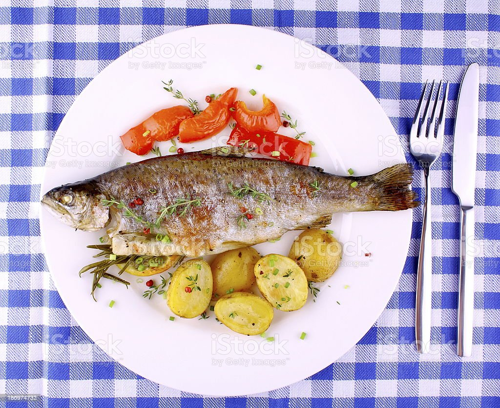 Grilled rainbow trout with red pepper, potato and lemon royalty-free stock photo