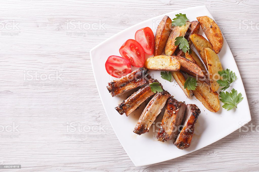 Grilled ribs, potatoes and tomatoes horizontal top view stock photo