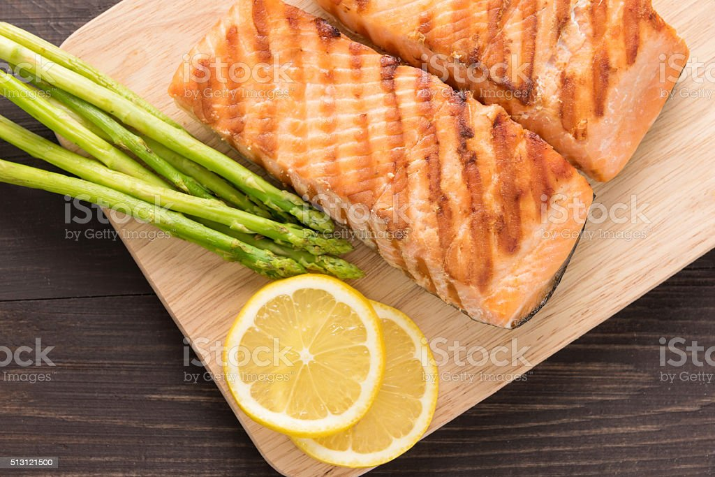 Grilled salmon and lemon, asparagus, on the wooden table stock photo