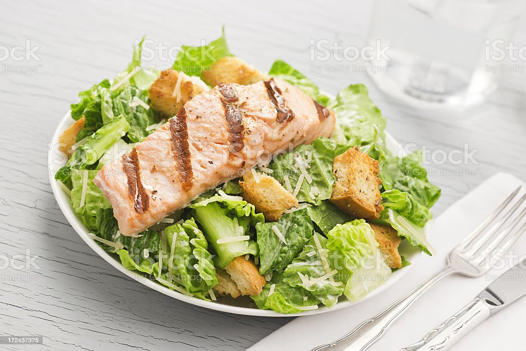 Grilled Salmon Caesar Salad on Table stock photo