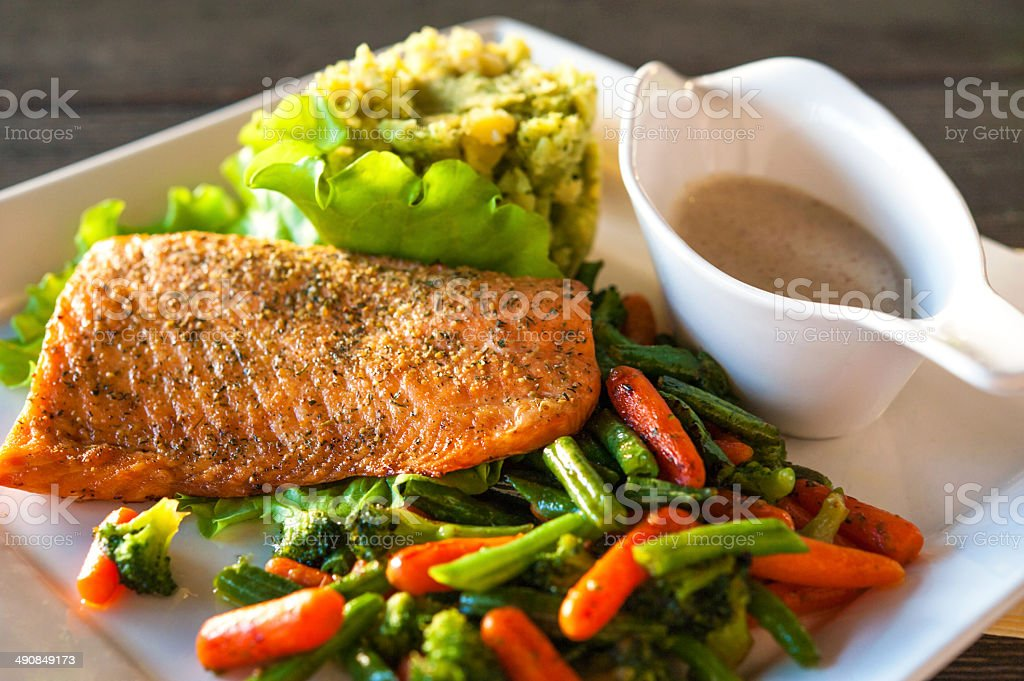 Grilled salmon fillet with potato-spinach mash and vegetables. stock photo