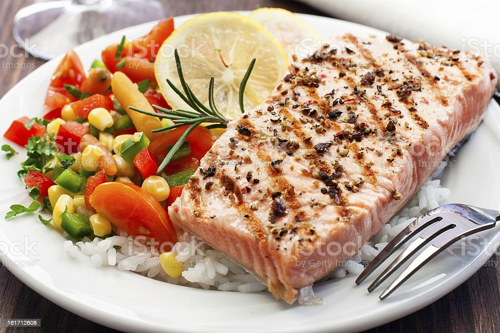 A grilled salmon followed by fresh rice and vegetables stock photo