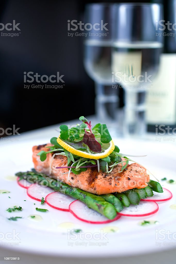 Grilled salmon on a bed of asparagus served on a white plate stock photo
