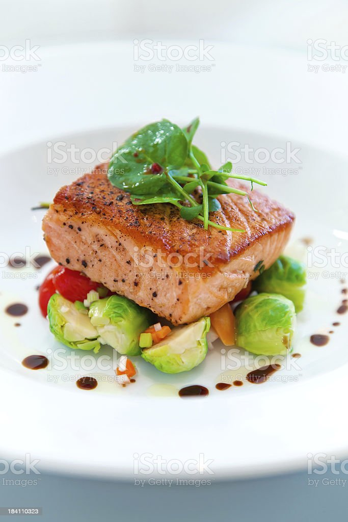 Grilled salmon on a bed of vegetables royalty-free stock photo