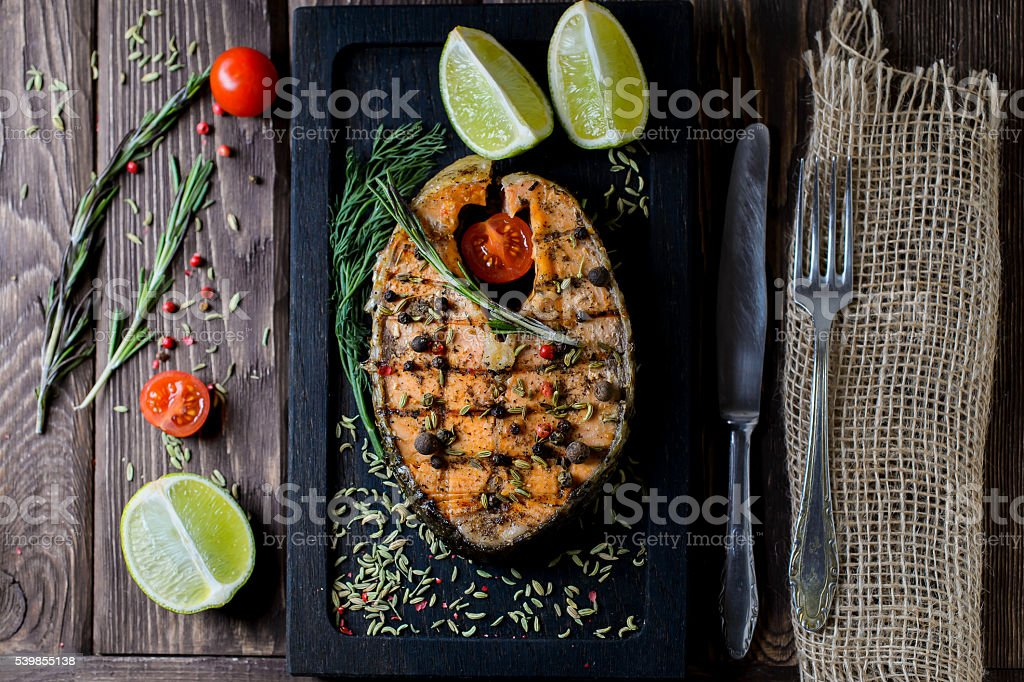 Grilled salmon on black board on wooden background stock photo