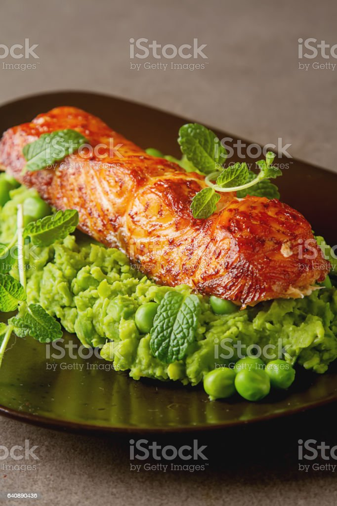 Grilled salmon pea puree decorated with mint on a brown plate. G stock photo