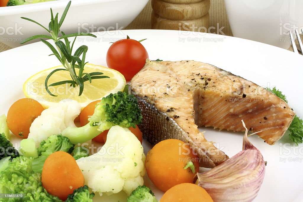 Grilled salmon steak and vegetables on white plate royalty-free stock photo