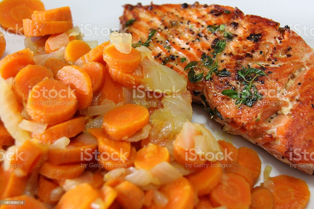 Grilled Salmon with buttery cooked onions and carrots stock photo