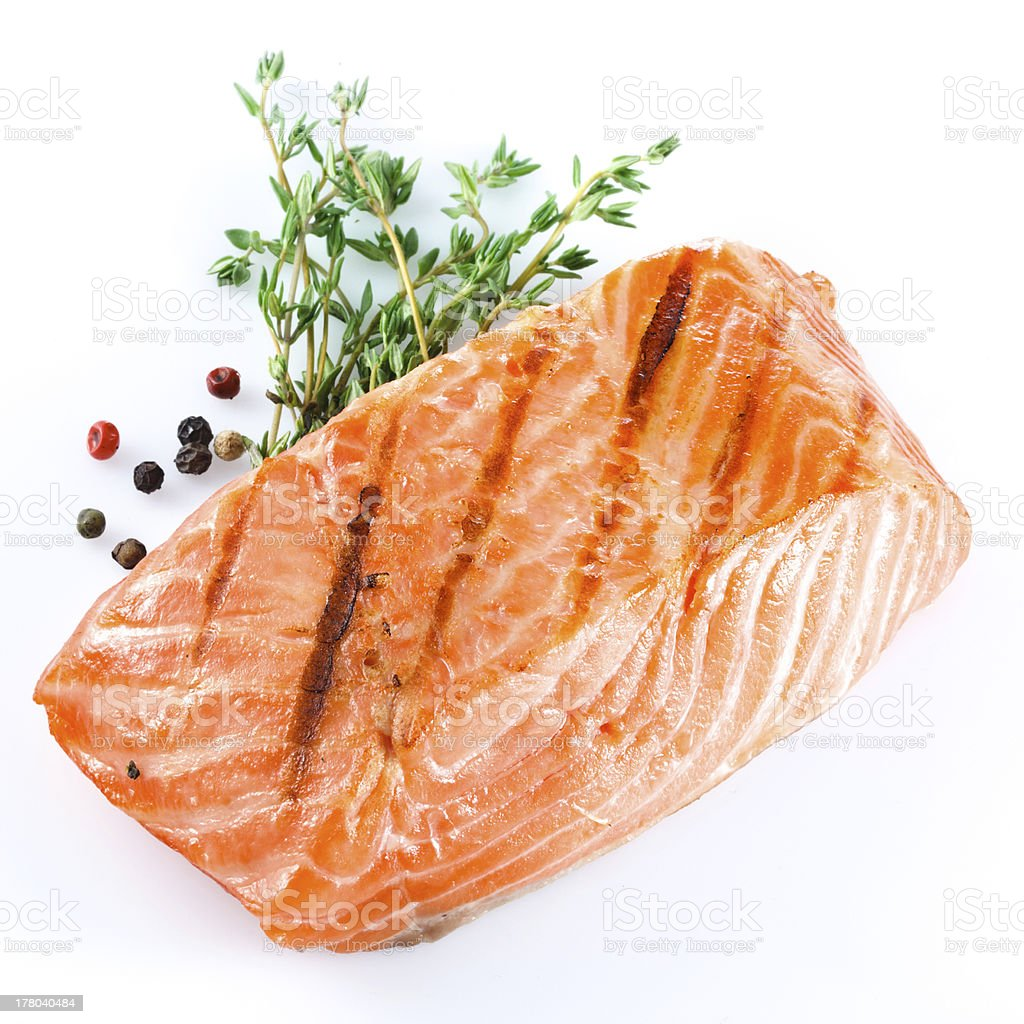Grilled salmon with herbs on white background stock photo